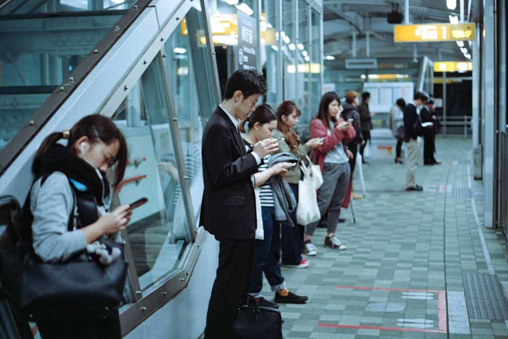 People at train station - Best earphones for commuting
