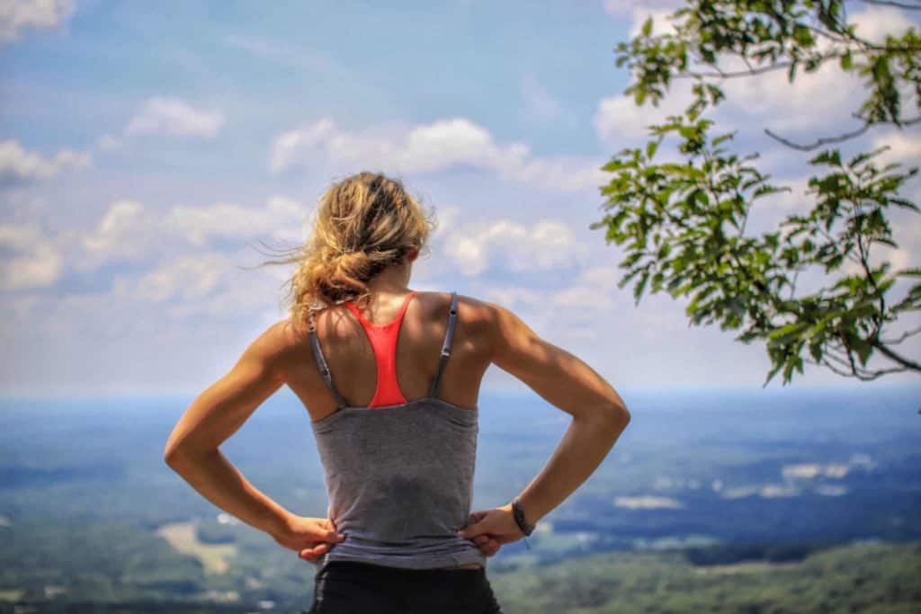 Woman after running standing with a view over landscape.