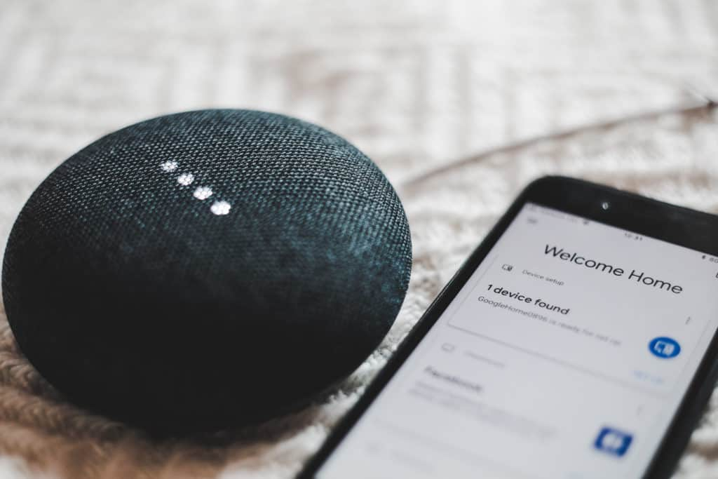 Google Home Speaker with iPhone and Google Nest Home App open
