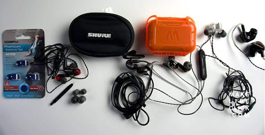 Looking down on a selection of in-ear monitors, cases and ear tips laid out on a table