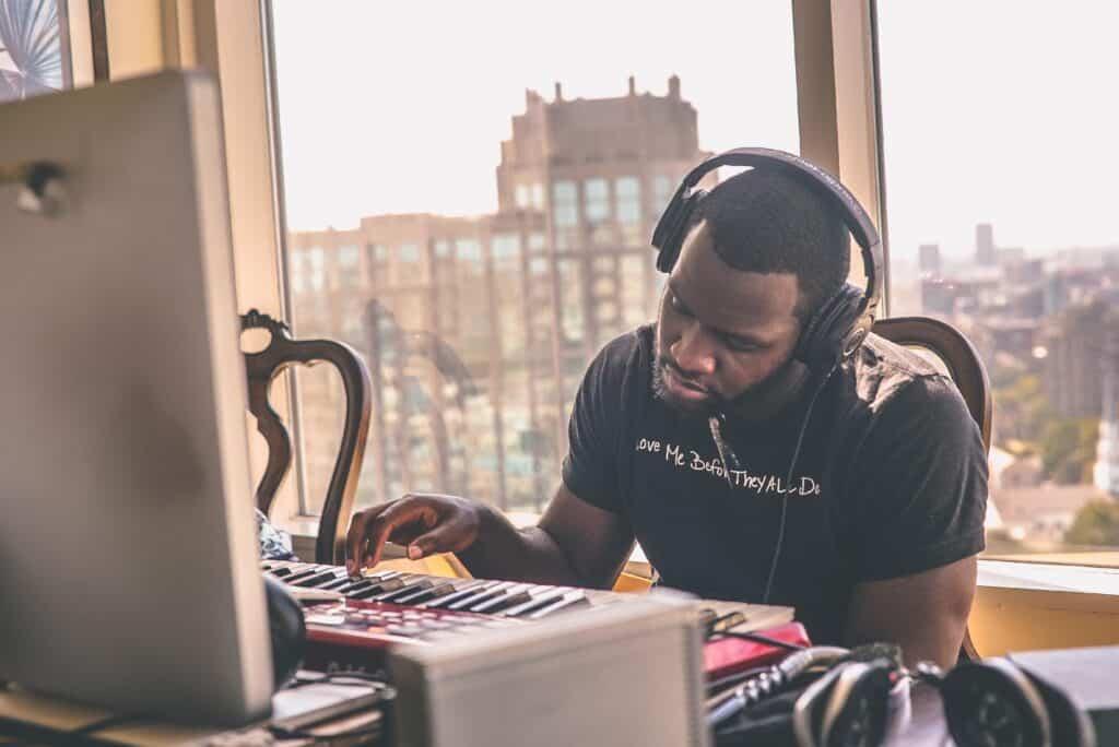 Man at computer mixing music - Open back vs closed back headphones
