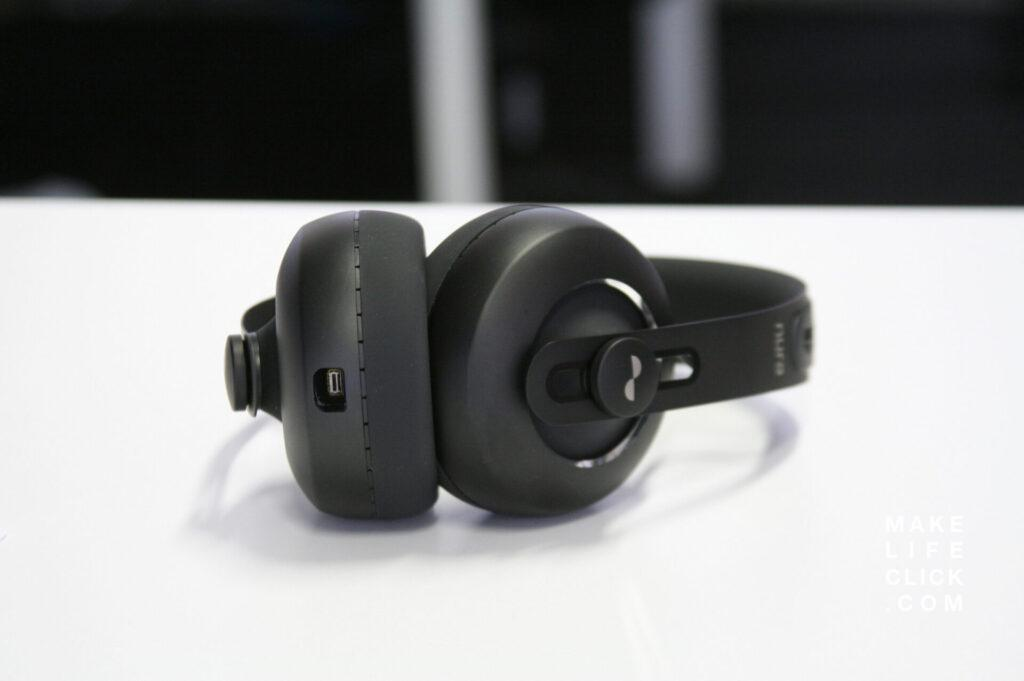 nuraphones review with headphones lying on a table with the view from the bottom showing the charging plug