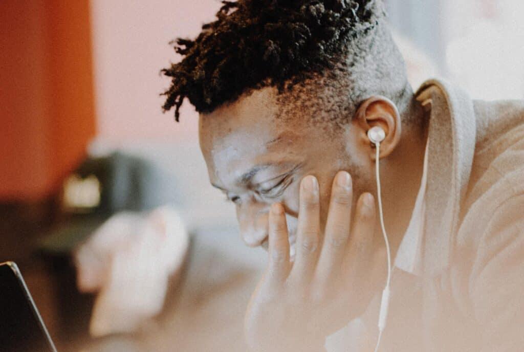 earphones on a man with laptop - IEM vs earphones