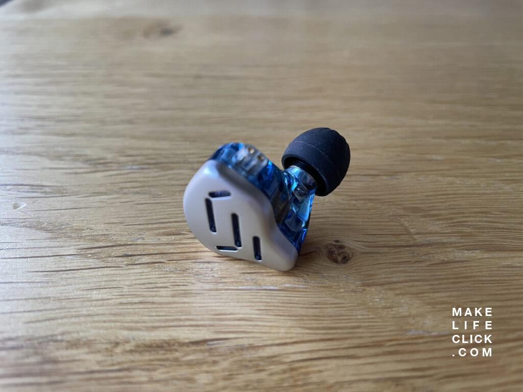 KZ Zax IEM single earbud lying on a table with an up-close photo showing detail of the design.