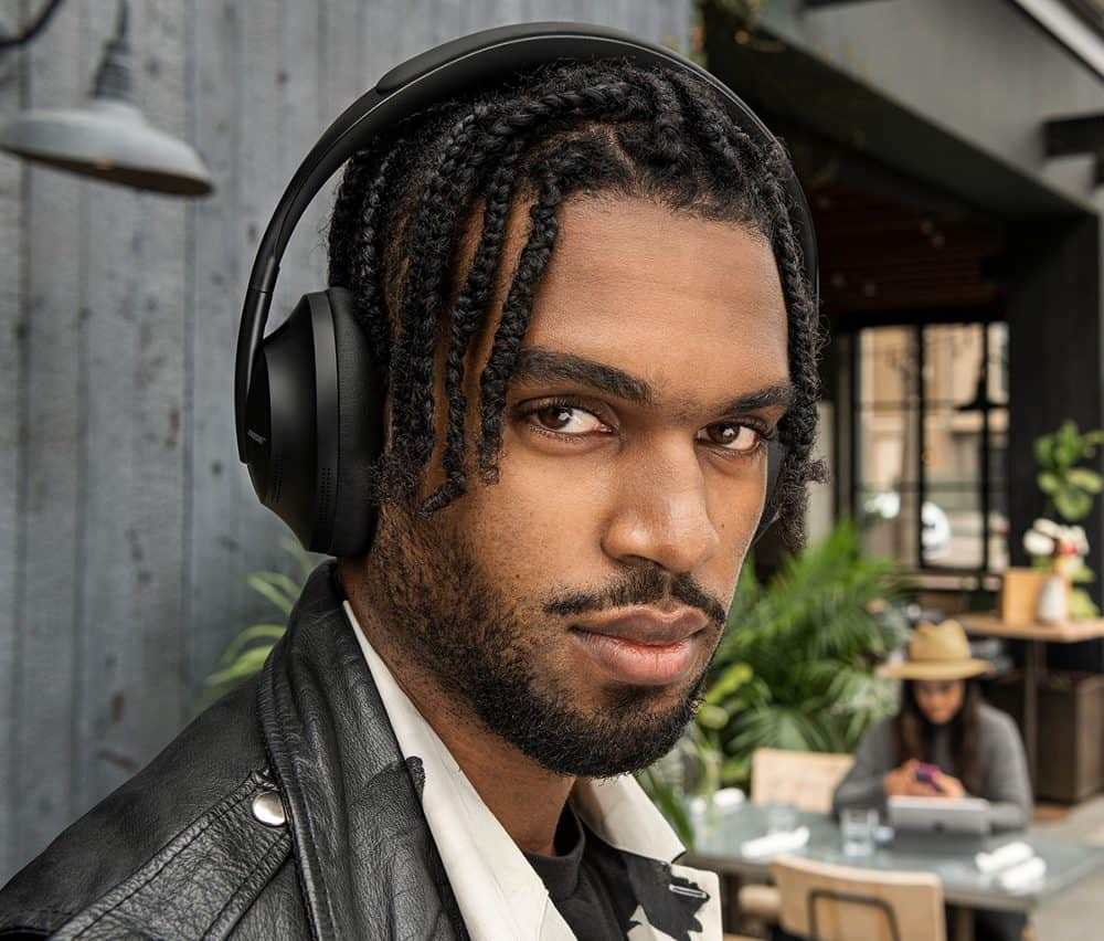 Bose Noise Canceling Headphones 700 being worn by a model in a mall restaurant