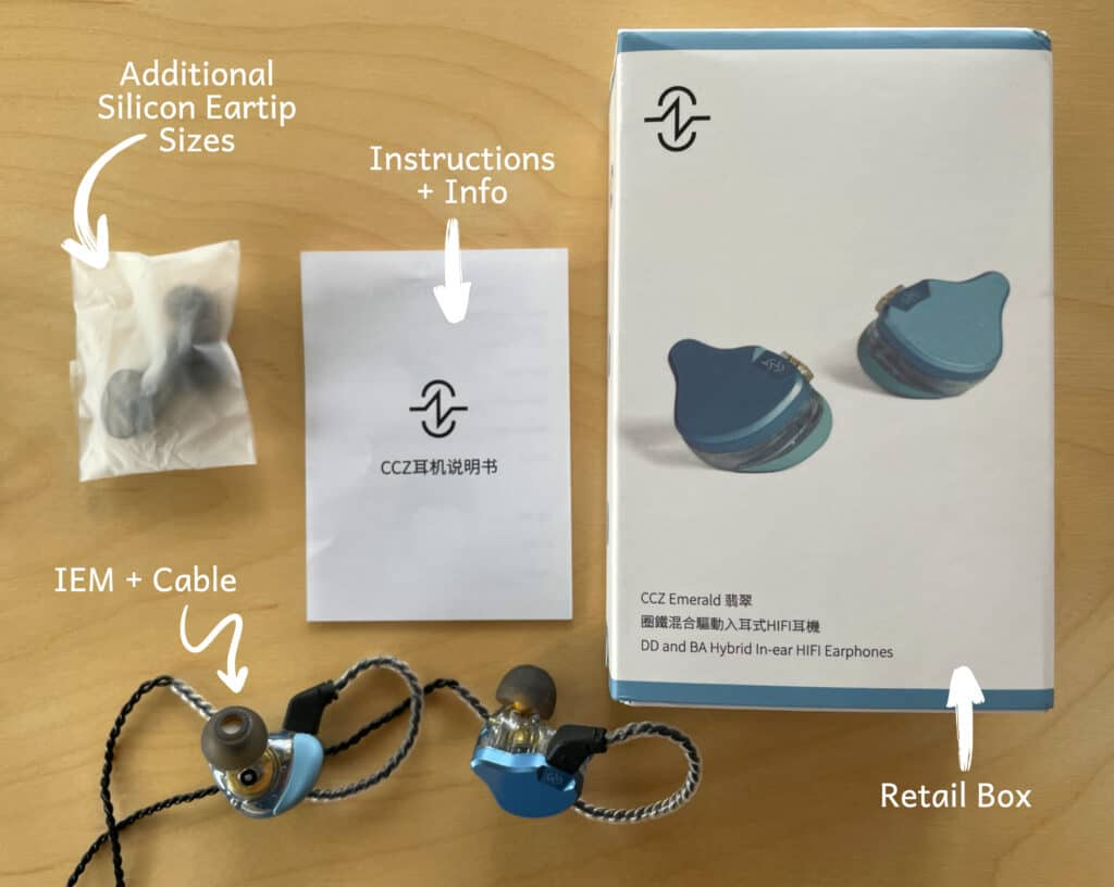 CCZ Emerald IEM with the included ccessories shown on a table - cable, eartips, in-ear, retail box and instruction manual