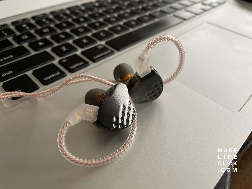 KB EAR Robin in-ear monitors earbuds up close sitting on a laptop keyboard